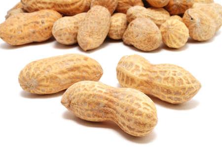cacahuate: Tres Cacahuetes aislados en blanco con muchos más en el fondo