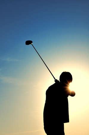 Silhouette of a man swinging a driver Reklamní fotografie