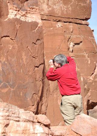 stone carving: Photographer Taking a Photo of Petroglyph  Along Potash Road Near Moab, Utah