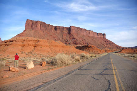 Middle-Aged Male Tourist Taking a Photograph of Parriott Mesa near Castle Valley, Utah