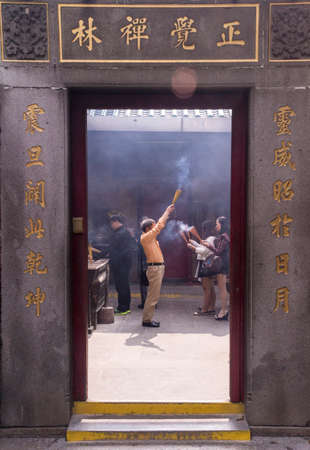 veneration: Chinese man in temple waving incense
