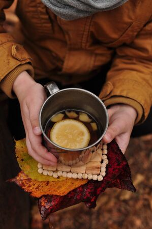 metal cup of tea with lemon and ginger in the hands of a man in a yellow jacket, on a wooden plate and with autumn leaves Stock fotó