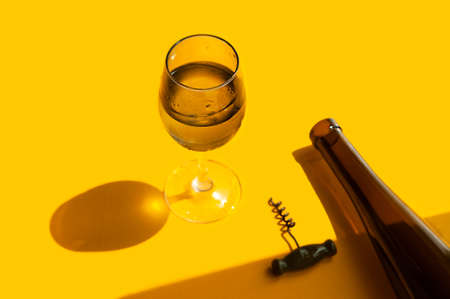 filled glass with water drops, dark glass wine bottle and corkscrew on a bright yellow background in natural light with sharp shadows, vertical image, summer bar menu