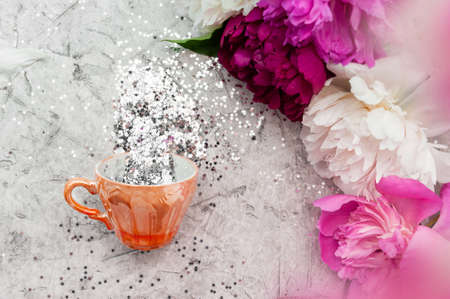 small gold cup filled with silver spangles stars and saucer on a light background with a bouquet of multi-colored peonies. Flat lay, top view,