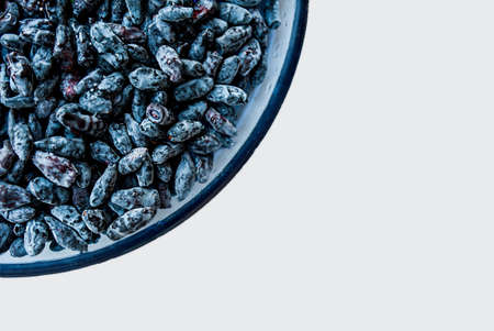 lot of the same ripe juicy blue honeysuckle berries in water droplets in a blue glass plate on a white table, top view. Berry background or Wallpaper with space for text