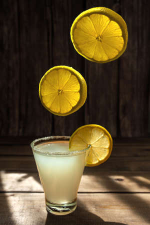 three round ripe juicy lemon slices fly and fall into a cocktail in a glass with sugar on the rim on wooden table, horizontal photo for the bar menu