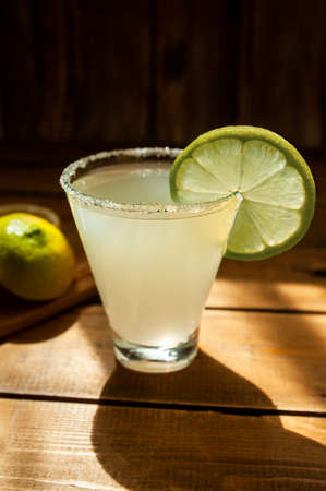 summer alcoholic yellow frosted drink in a transparent shaped glass with sugar on the rim and a round ripe juicy lime slice on a wooden table, horizontally, photo for the bar menu Фото со стока