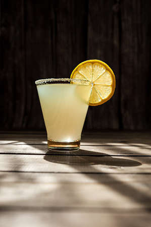 summer alcoholic yellow frosted drink in a transparent shaped glass with sugar on the rim and a round ripe juicy slice of lemon on a wooden table, photo for the bar menu Фото со стока