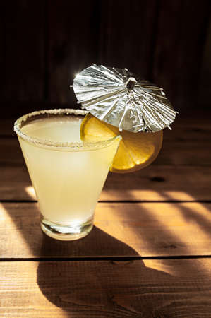 summer alcoholic yellow drink in transparent shaped glass with sugar on the rim, silver decor umbrella and round ripe juicy lime slice on wooden table, horizontally, photo for the bar menu