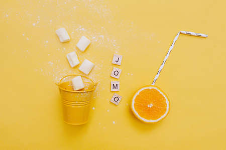 Abbreviation word JOMO written on of wood eco-friendly letters and festive cocktail tube in juicy ripe orange and marshmallows from a small yellow bucket a bright yellow background Banco de Imagens