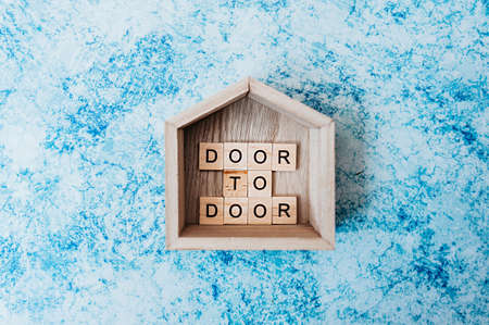 inscription door to door of wooden letters in wooden decor small house with on a gray-blue cement background. contactless delivery and social distancing in the new normal time Layout