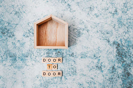 wooden decor small house with an inscription door to door of wooden letters on a gray-blue cement background. contactless delivery and social distancing in the new normal time Layout Archivio Fotografico