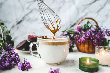 metal kitchen whisk whips up coffee foam in a large glass Cup with milk on a white marble surface with a burning candle, a wicker basket with a lush bouquet of purple lilacs. dalgona coffee recipe Imagens