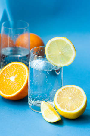 two glasses of sparkling clear water with bubbles and lemon and ripe citrus fruits lemon andoranges in a cut and whole on a blue background. take vitamin C, strengthening immunity
