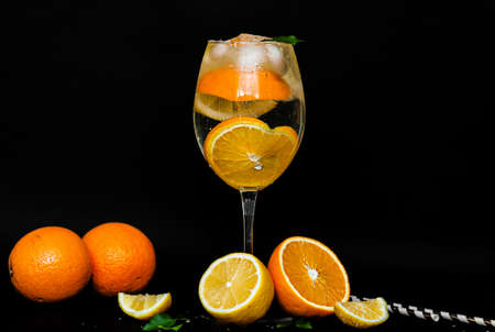 transparent glass with a citrus cocktail. Drops of water and condensate flow down a glass with a drink with oranges, lemon, ice and mint on a black background. Image for menu, bar content Banque d'images