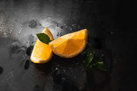 juicy little pieces of lemon in drops with a mint leaf on a black wet glass surface