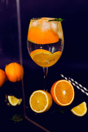 transparent glass with a citrus cocktail. Drops of water and condensate flow down a glass with a drink with oranges, lemon, ice and mint on a black background. Image for menu, bar content