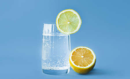 translucent glass of water with gases and bubbles, with a round slice of lemon on a glass and a whole lemon on blue background. Refreshment in the heat. Healthy lifestyle and nutrition Banque d'images