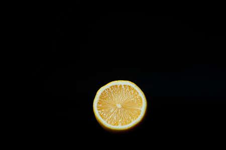 half a juicy yellow ripe fresh lemon on a pure black background
