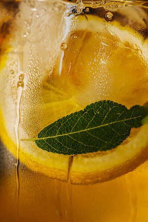 drops of water and condensation smudges flow down a transparent glass with a cold drink, a round slice of a lemon and a mint leaf. Vertical, selective focus, art image