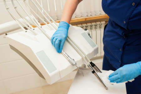 doctor without a face in a blue uniform and blue gloves wipes dental equipment in a hospital
