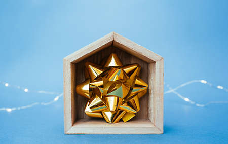 gold foil decor bow inside a wooden toy empty house and garlands on a blue background at the back. Imagens