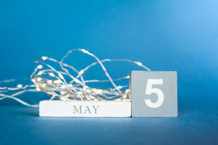 Wooden cubes of a calendar with the date may 5 and glowing garlands with warm yellow light on a blue background. Banque d'images