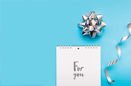 notebook on a spiral with white sheets and black lettering for you and a blue background with a silver foil bow and silver curly ribbons