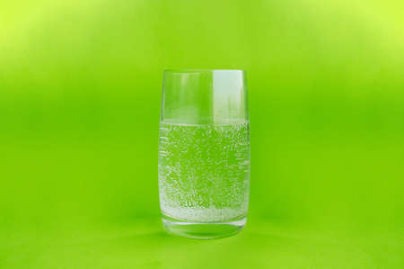 banner about a healthy lifestyle. Clear glass water glass full of pure carbonated water with bubbles on a clear green background. Zdjęcie Seryjne