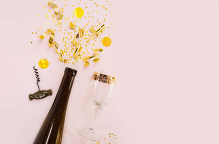 Golden streamer, sequins, gold spirals and stars explodes and fly up like fireworks from the neck of a bottle of dark glass, glass with a gold border and a wine opener in the beige background.