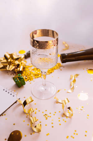 glass with a gold border with yellow circles and gold spirals serpentines, dark glass bottle and a wine opener in the background.