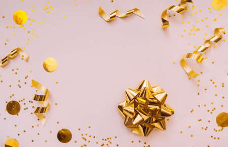 gold foil bow for decoration on a delicate beige background with yellow circles and gold spirals serpentines. layout for gifts, greetings, and sales.