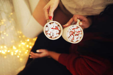 two cups of hot cocoa with marshmallows and sprinkles in hands of two girls with neat manicure and knitted sweatshirts without faces against background of many burning lights and bulbs Foto de archivo