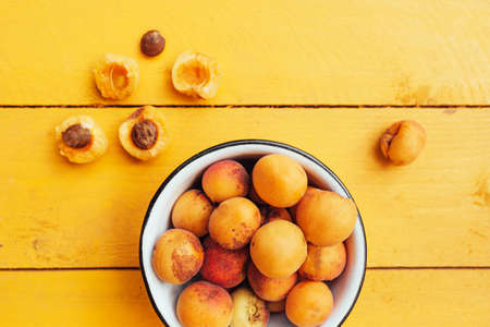 ripe juicy homemade apricots with cracks and flaws in the plate and scattered on a bright yellow wooden surface. Harvest 2020