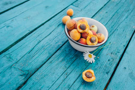 ripe juicy homemade apricots with cracks and flaws in the plate and scattered on a bright turquoise wooden cover with chamomile. Harvest 2020
