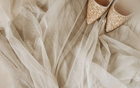 shining gold shoes on soft soft beige tulle fabric, festive mock up, selective focus