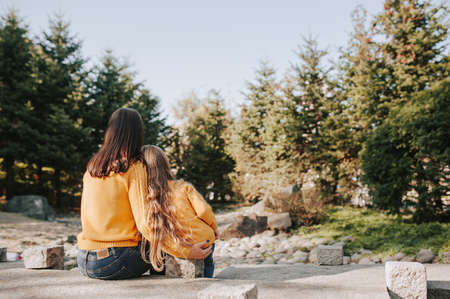 mother and daughter with long blonde hair in identical yellow knitted warm sweaters tenderly embrace and admire autumn forest and trees in stone garden, rear view