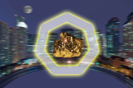 resourse: Nugget of precious yellow metal against a night panorama of a city Stock Photo