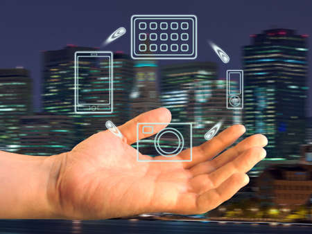 Various devices over a palm against a panorama of a night sity Stock Photo - 13282982