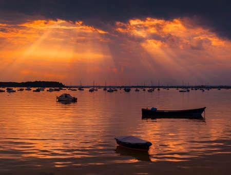Crepuscualr rays of sunlight shine onto still waters of Poole Harbour near Sandbanks, Poole, Bournemouth, Dorset