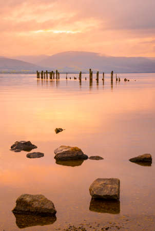 Long exposure of a Scottish loch and jetty. The mountains of the Trossachs surround the loch photo