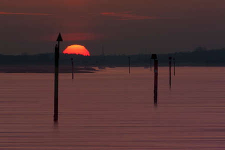 deep orange: The deep, orange Sun sets over the Beaulieu River at Lepe through deep channel markers