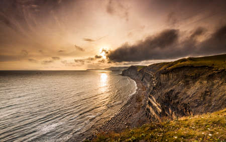 The sky clears after a rain storm and the sun burns through clouds over the South Dorset jurassic coastline photo