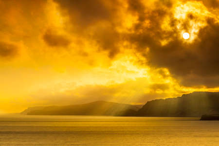 The sky clears after a rain storm and the sun burns through clouds over the South Dorset jurassic coastline Stock Photo