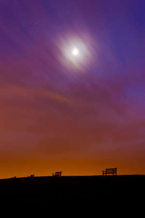 hilltop: Light polution produces an orange glow above lonely, empty benches on a hilltop near Weymouth