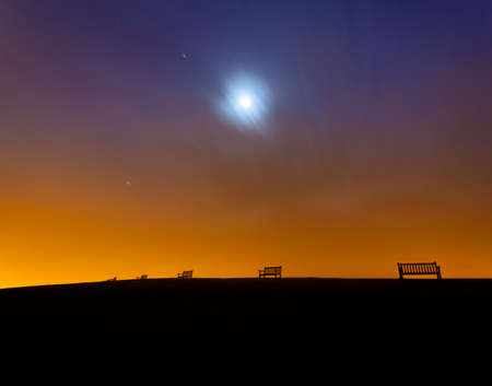 Light polution produces an orange glow above lonely, empty benches on a hilltop near Weymouth photo
