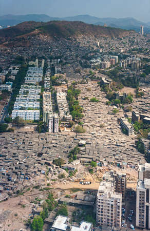 The slums of Mumbai, seen from the air, fill every gap between larger residential buildings and offices