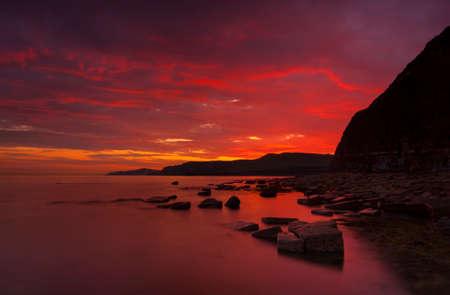 glistening: El sol se pone en la hermosa costa de Dorset iluminando relucientes rocas con reflejos anaranjados y amarillos
