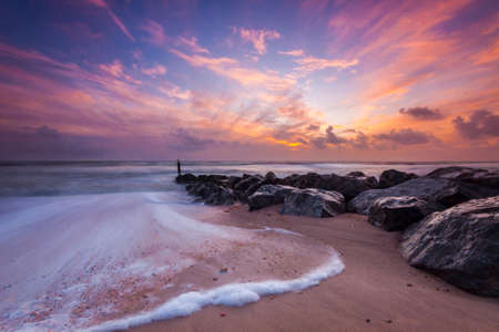 Beautiful sunet on the Dorset coast. Ocean waves batter the sea defences photo