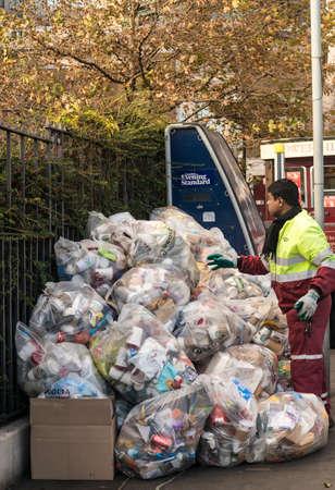 recolector de basura: Bolsas de basura en una calle de Londres con el recolector de basura se acumulan bolsas